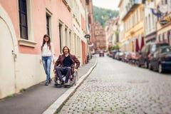 Pares jovenes en la silla de ruedas que da un paseo en la ciudad Fotos de archivo libres de regalías