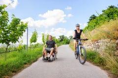 Pares jovenes en la silla de ruedas que disfruta de tiempo al aire libre Fotos de archivo libres de regalías