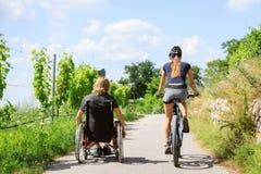 Pares jovenes en la silla de ruedas que disfruta de tiempo al aire libre imagenes de archivo
