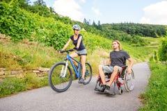 Pares jovenes en la silla de ruedas que disfruta de tiempo al aire libre fotografía de archivo libre de regalías