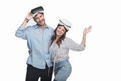 Pares jovenes en las auriculares de la realidad virtual que se colocan de abarcamiento y sonrientes en la cámara Imagen de archivo