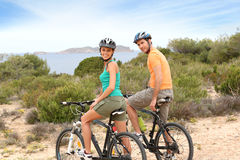 Pares jovenes en las bicis que visitan las islas Foto de archivo