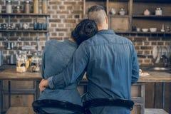Pares jovenes en las camisas del dril de algodón que sientan el abarcamiento en la tabla de madera y desayunar Fotografía de archivo