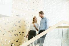 Pares jovenes en las escaleras en la oficina Imagen de archivo libre de regalías
