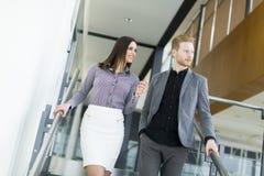 Pares jovenes en las escaleras en oficina Foto de archivo libre de regalías