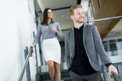 Pares jovenes en las escaleras en oficina Imagen de archivo libre de regalías