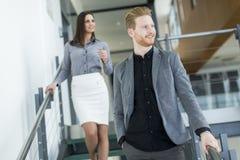 Pares jovenes en las escaleras en oficina Fotos de archivo libres de regalías
