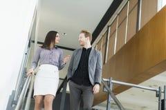Pares jovenes en las escaleras en oficina Imagen de archivo