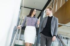 Pares jovenes en las escaleras en oficina Fotografía de archivo libre de regalías