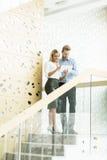 Pares jovenes en las escaleras en oficina Fotos de archivo