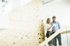 Pares jovenes en las escaleras en oficina Fotografía de archivo