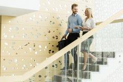 Pares jovenes en las escaleras en oficina Imágenes de archivo libres de regalías