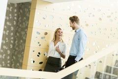 Pares jovenes en las escaleras en oficina Imagenes de archivo