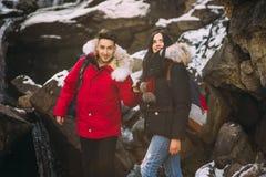 Pares jovenes en las montañas en invierno Fotos de archivo