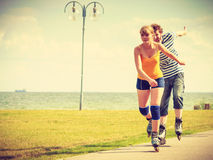 Pares jovenes en los pcteres de ruedas que montan al aire libre Imagen de archivo libre de regalías