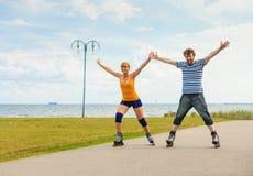 Pares jovenes en los pcteres de ruedas que montan al aire libre Foto de archivo libre de regalías