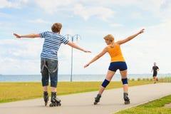 Pares jovenes en los pcteres de ruedas que montan al aire libre Fotografía de archivo libre de regalías