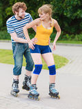 Pares jovenes en los pcteres de ruedas que montan al aire libre Foto de archivo