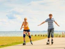 Pares jovenes en los pcteres de ruedas que montan al aire libre Imagenes de archivo