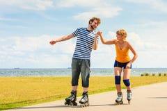 Pares jovenes en los pcteres de ruedas que montan al aire libre Fotos de archivo