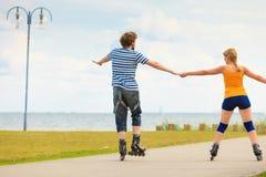Pares jovenes en los pcteres de ruedas que montan al aire libre Imagen de archivo