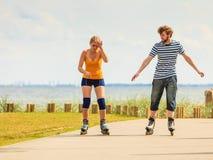 Pares jovenes en los pcteres de ruedas que montan al aire libre Fotografía de archivo