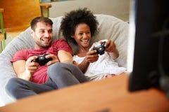 Pares jovenes en los pijamas que juegan al videojuego junto Foto de archivo