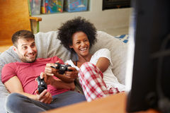 Pares jovenes en los pijamas que juegan al videojuego junto Imagenes de archivo