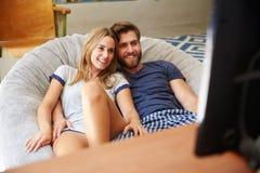 Pares jovenes en los pijamas que miran la televisión junto Foto de archivo