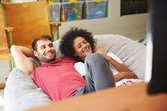 Pares jovenes en los pijamas que miran la televisión junto Imagenes de archivo