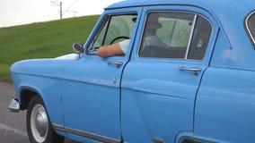 Pares jovenes en los sombreros que conducen en el coche retro azul después de lluvia durante viaje del verano Pares irreconocible almacen de metraje de vídeo