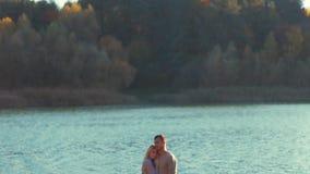 Pares jovenes en los suéteres elegantes acogedores que se colocan en la orilla del río que abraza con amor Historia de amor, para almacen de video