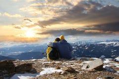 Pares jovenes en montañas de la nieve Imagen de archivo libre de regalías