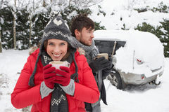 Pares jovenes en nieve con el coche Imágenes de archivo libres de regalías