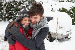 Pares jovenes en nieve con el coche Foto de archivo libre de regalías