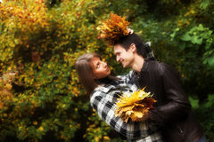Pares jovenes en parque del otoño foto de archivo