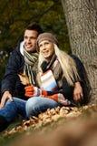 Pares jovenes en parque en el otoño Fotos de archivo libres de regalías