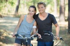 Pares jovenes en paseo de la bici en bosque Imagen de archivo