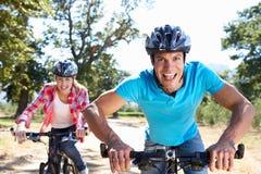 Pares jovenes en paseo de la bici a través del país Imagen de archivo libre de regalías