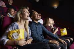 Pares jovenes en película del cine y palomitas de observación de la consumición Fotos de archivo libres de regalías