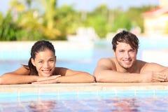 Pares jovenes en piscina Fotos de archivo libres de regalías