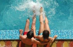 Pares jovenes en piscina de agua Fotos de archivo