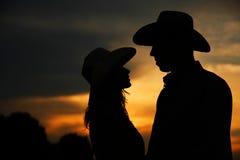Pares jovenes en silueta del amor en sombreros de vaquero Imágenes de archivo libres de regalías