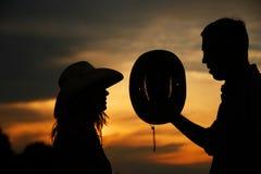 Pares jovenes en silueta del amor en sombreros de vaquero Foto de archivo libre de regalías