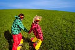 Pares jovenes en snowboard del sportwear en la hierba en el verde Imágenes de archivo libres de regalías