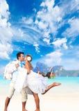 Pares jovenes en su boda de playa Imágenes de archivo libres de regalías