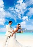 Pares jovenes en su boda de playa Imagen de archivo