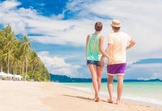 Pares jovenes en su luna de miel que se divierte por la playa tropical Imagenes de archivo