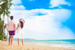 Pares jovenes en su luna de miel que se divierte por la playa tropical Imagen de archivo libre de regalías