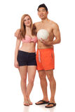 Pares jovenes en traje de baño con voleibol Fotografía de archivo libre de regalías